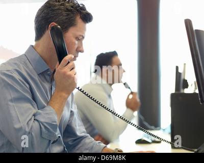 Businessman talking on phone at desk - Stock Photo