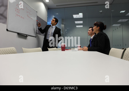 Businessman using whiteboard in meeting - Stock Photo