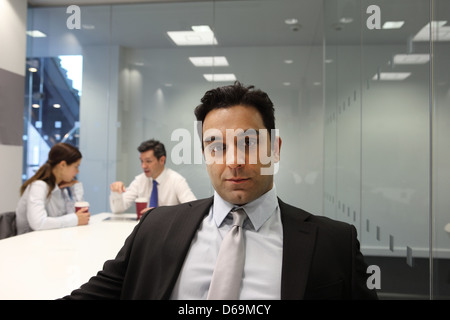 Businessman sitting in meeting room - Stock Photo