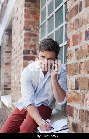Man on cell phone taking notes - Stock Photo