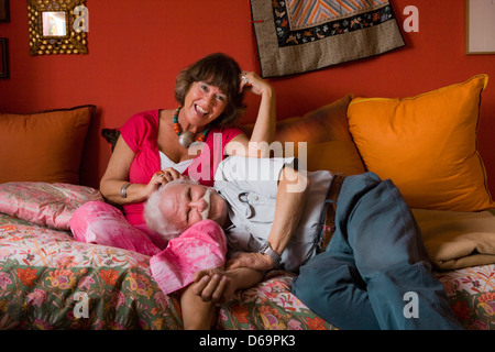 Smiling couple relaxing on sofa - Stock Photo