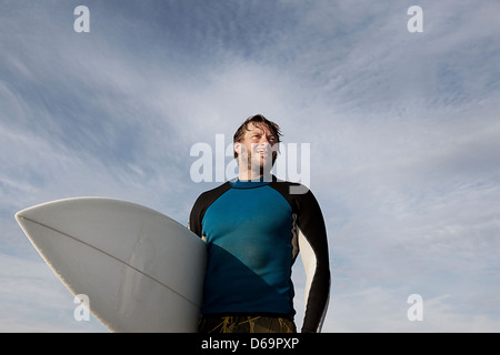 Surfer carrying board outdoors - Stock Photo