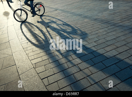 Bicycle casting shadow on city street - Stock Photo