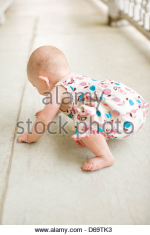 Baby girl trying to stand on carpet - Stock Photo