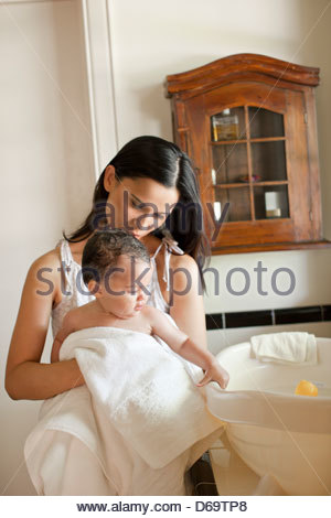 Mother drying off baby girl after bath - Stock Photo