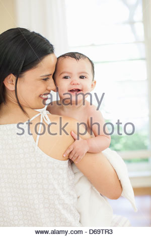 Mother holding baby girl after bath - Stock Photo