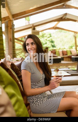 Smiling woman eating in cabana tent - Stock Photo