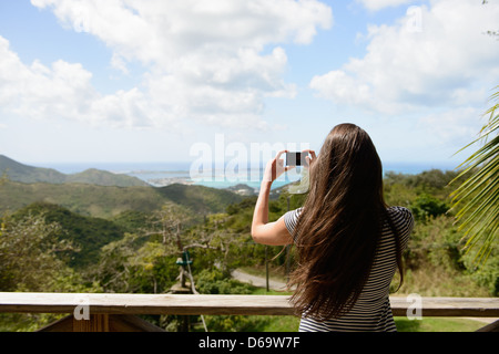 Woman taking picture of coast landscape - Stock Photo