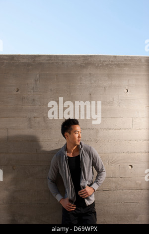 Man leaning on concrete wall - Stock Photo
