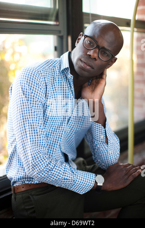 Businessman sitting on windowsill - Stock Photo