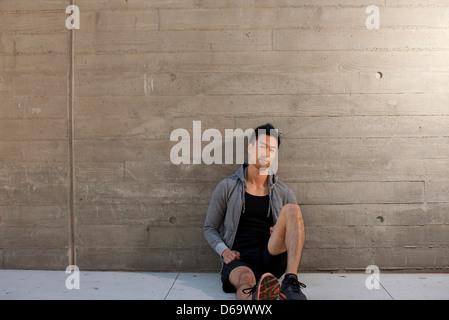 Runner sitting on city street - Stock Photo