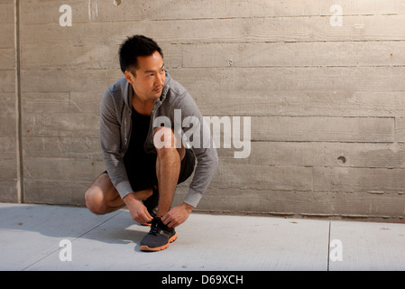 Runner tying shoes on city street - Stock Photo