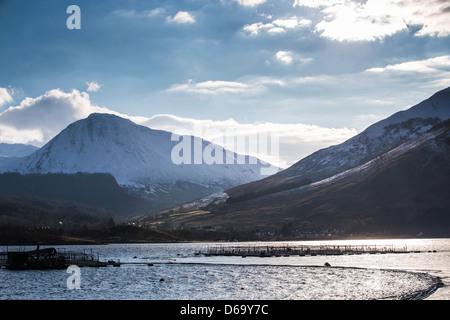 Snowy mountains over rural lake - Stock Photo