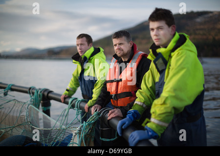 Workers at salmon farm in rural lake - Stock Photo