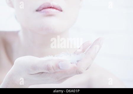 Close up of woman?s hands with feathers - Stock Photo