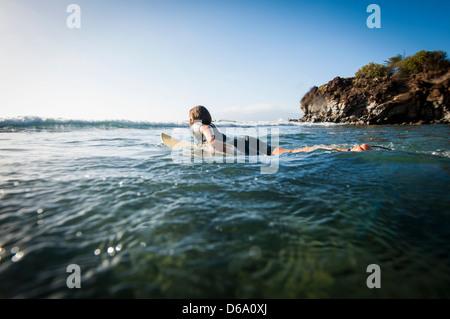 Surfer paddling in ocean - Stock Photo