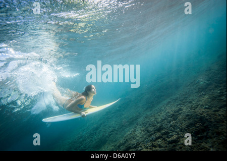 Surfer diving under wave in water - Stock Photo
