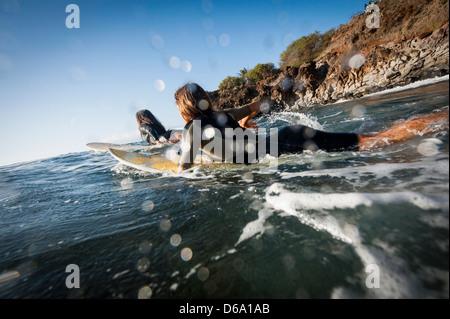 Surfers paddling in ocean - Stock Photo