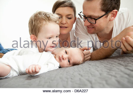 Family laying together on bed - Stock Photo