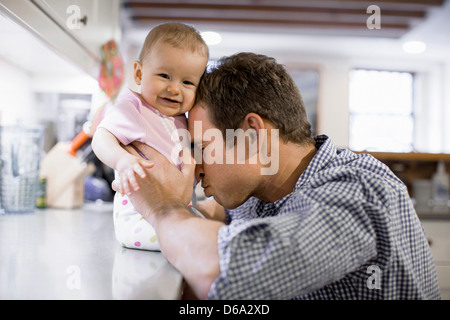 Father with baby daughter in kitchen - Stock Photo