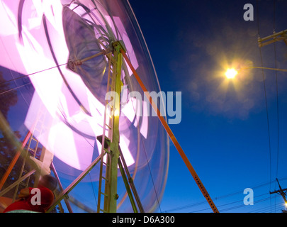 Urban Street Fair with Ferris Wheel in Light Motion Pattern - Street Light and Electrical Poles hanging overhead - Stock Photo