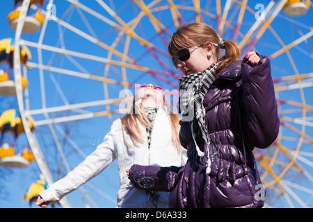 Teenage girls against a ferris wheel - Stock Photo