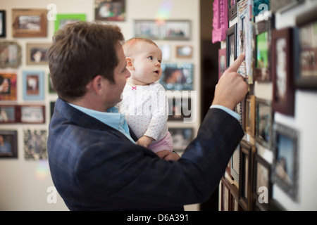 Businessman and baby looking at pictures - Stock Photo