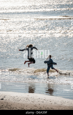 Summer afternoon: a rear view of two young children girls playing jumping splashing in the sea, UK - Stock Photo