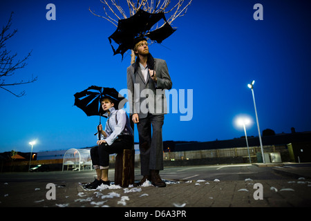 2 actors performing as Vladimir & Estragon in Samuel Beckett's classic play 'Waiting for Godot' in a deserted carpark - Stock Photo