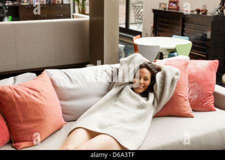 Smiling woman relaxing on sofa - Stock Photo