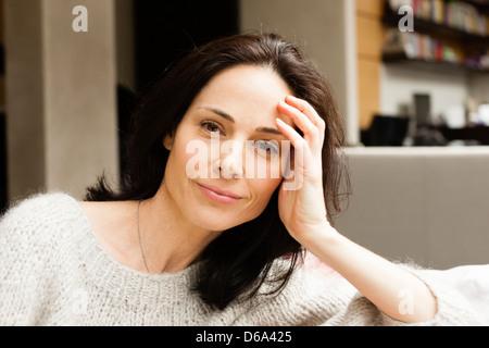 Smiling woman sitting on sofa - Stock Photo