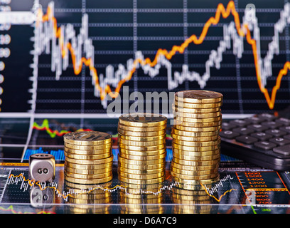 Uptrend stacks coins, dices cube with the word GO and calculator on the financial stock charts as background. Selective - Stock Photo