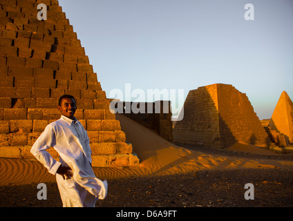 Young Sudanese Man In Front Of The Pyramids And Tombs In Royal Cemetery, Meroe, Sudan - Stock Photo