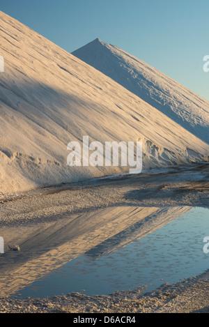 Sunrise over salt piles, salt industry - Stock Photo