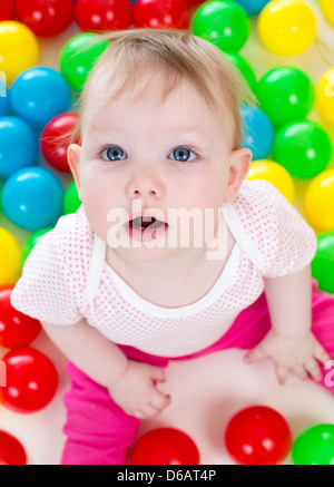 Portrait of funny baby playing among colorful balls - Stock Photo