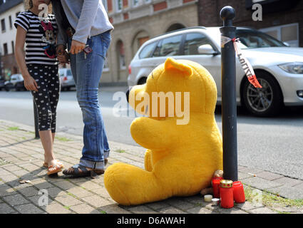 A woman and a girl put down a huge teddybear and a candle in front of a house where a boy was stabbed to death in - Stock Photo