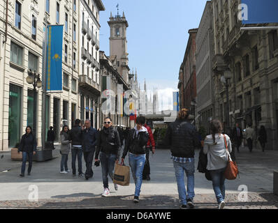 People walk by a pedestrian zone in front of the Milan Cathedral, Duomo di Santa Maria Nascente, in  Milan, Italy, - Stock Photo