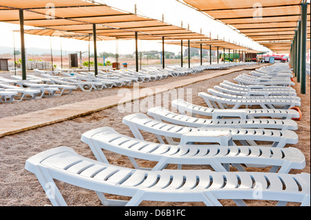 Beach chairs under a canopy on a sandy beach - Stock Photo