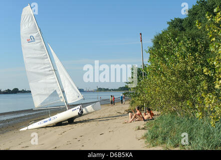 A catamaran and some bathers lie on a beach of the river island Harriersand in the Weser between Bremen and Brake, - Stock Photo