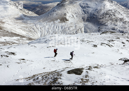 Hillwalkers descending the slopes of Beinn Luibhean with the Cobbler (884m) right and slopes of Beinn Narnain (926m) - Stock Photo