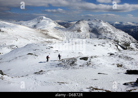 Hillwalkers descending the slopes of Beinn Luibhean with the Cobbler (884m) on the right and Beinn Narnain (926m) - Stock Photo