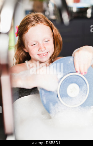 Smiling girl washing plate in sink - Stock Photo