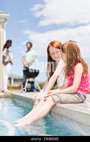 Girls dangling feet in swimming pool - Stock Photo