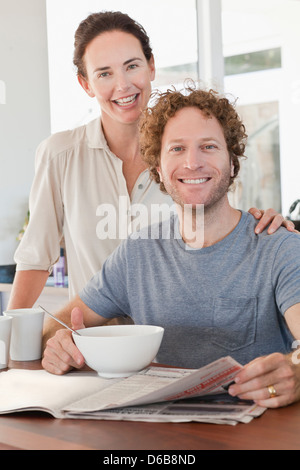 Couple reading newspaper at breakfast - Stock Photo