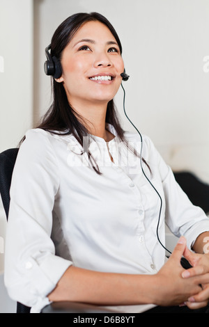 Businesswoman wearing headset at desk - Stock Photo
