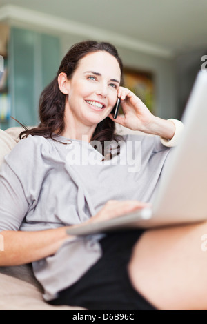 Woman on cell phone using laptop - Stock Photo