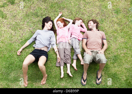 Family laying in grass together - Stock Photo