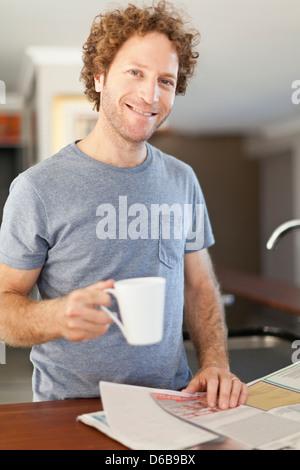 Man reading newspaper at breakfast - Stock Photo