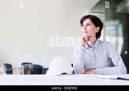 Businesswoman thinking at desk - Stock Photo