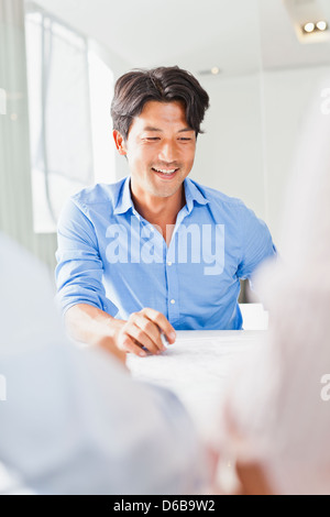 Businessman sitting in meeting - Stock Photo